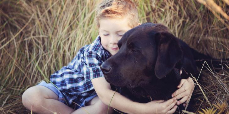 niño abrazando perrito negro