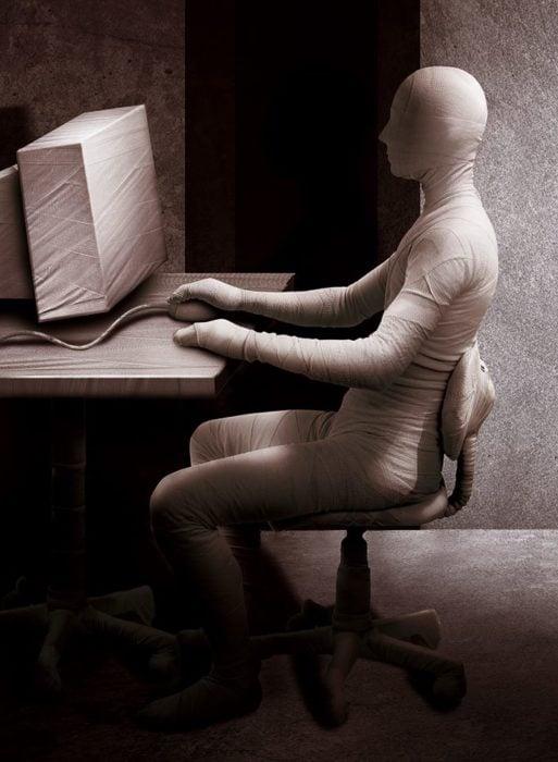 hombre en computador enredado en vendas