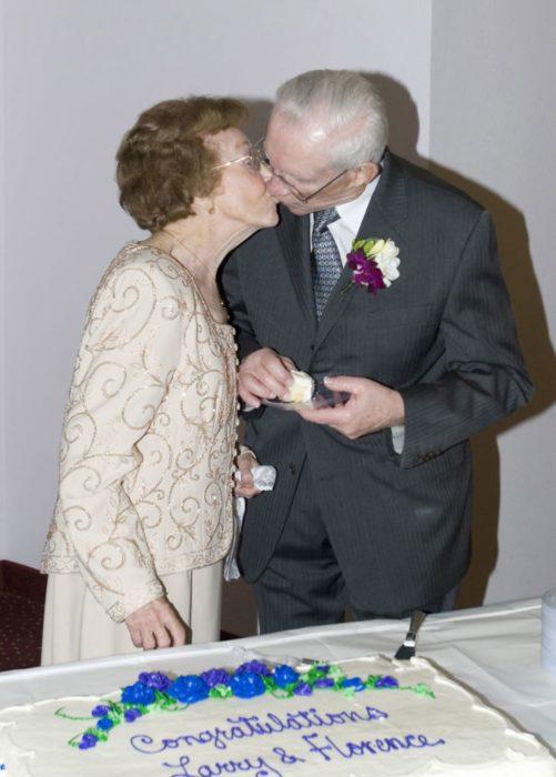 ancianso besándose detrás de un pastel