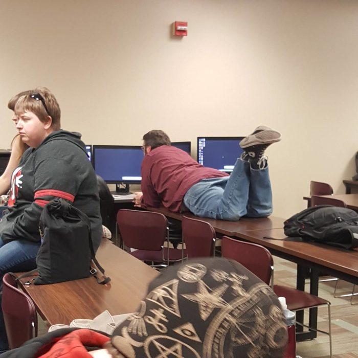 hombre recostado en una banca frente a tres computadoras