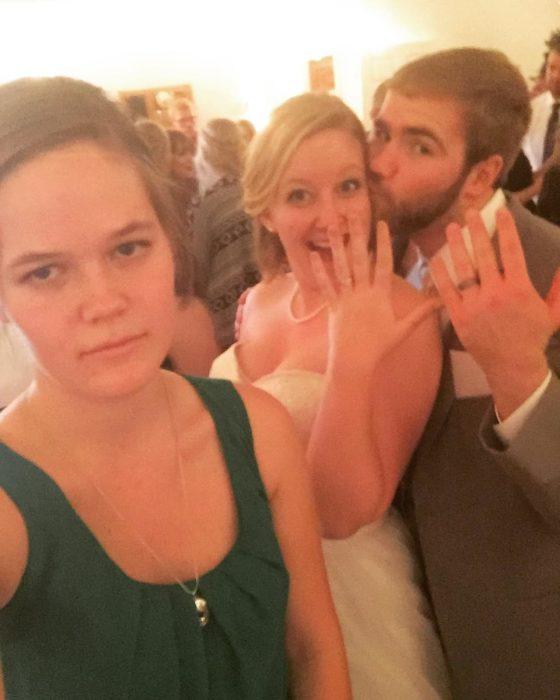 chica con cara de molesta frente a pareja de novios en su boda