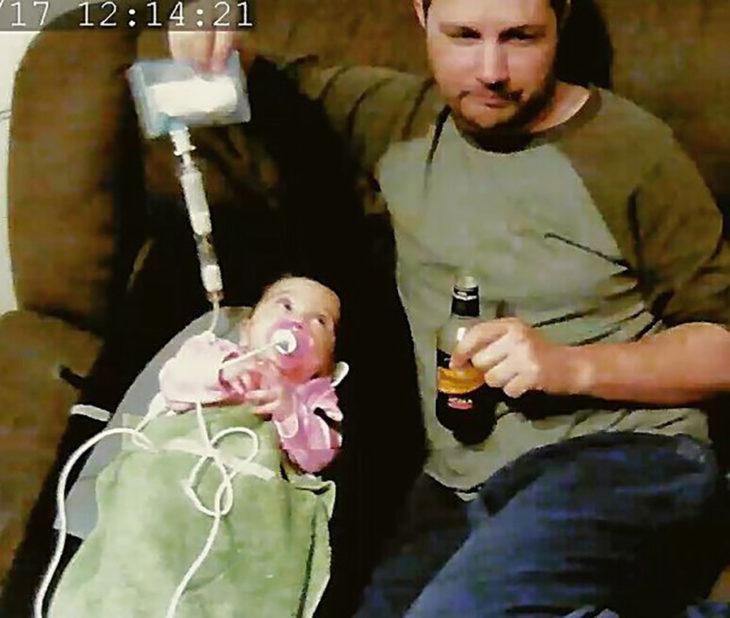 hombre con cerveza e la mano y sonda con leche por la que alimenta al bebé