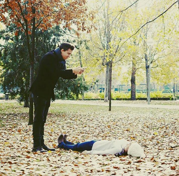 mujer recostada sobre las hojas mientras hombre le toma foto