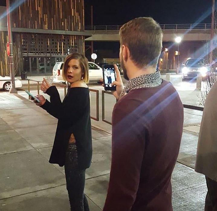 chico tomando una foto a su novia bajo la luz de la calle