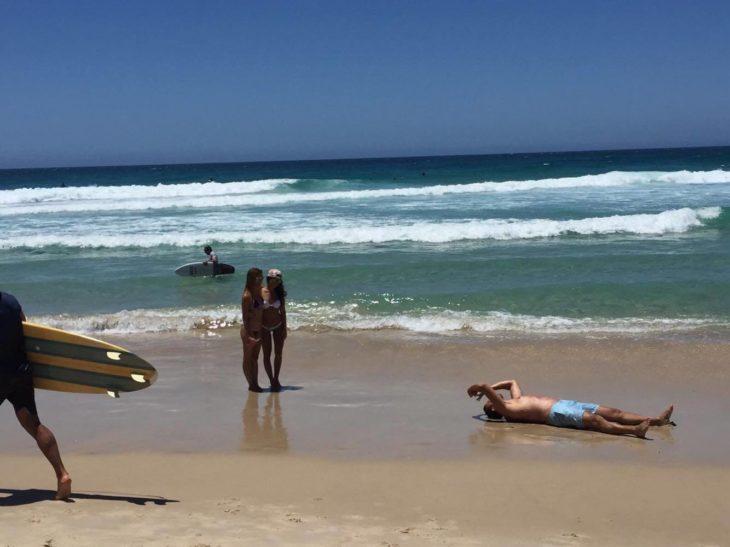 chico tirado en la arena tomando foto de su novia