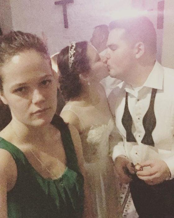 chica con cara de molesta frente a pareja de recién casados