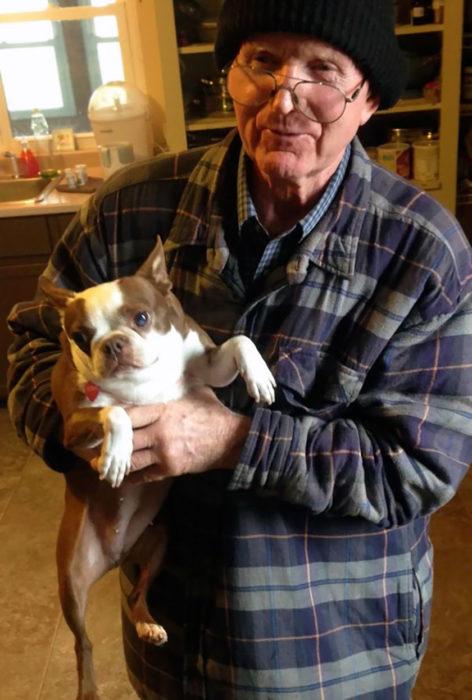 anciano cargando un perro