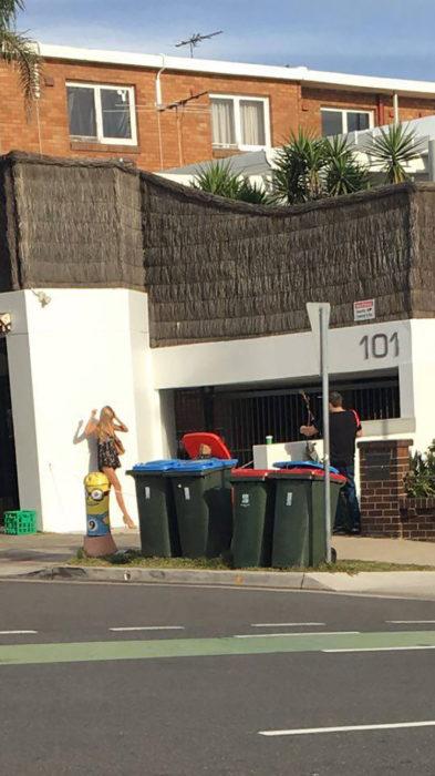 hombre tomando fotos a mujer al lado de botes de basura