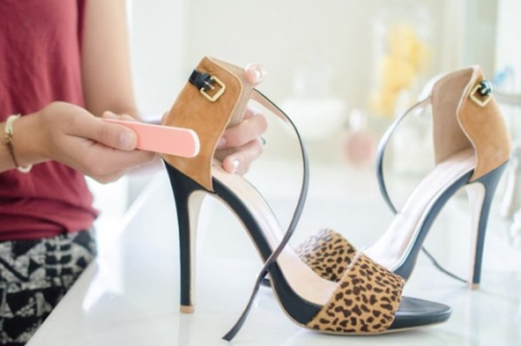 mujer limando sandalias de gamuza
