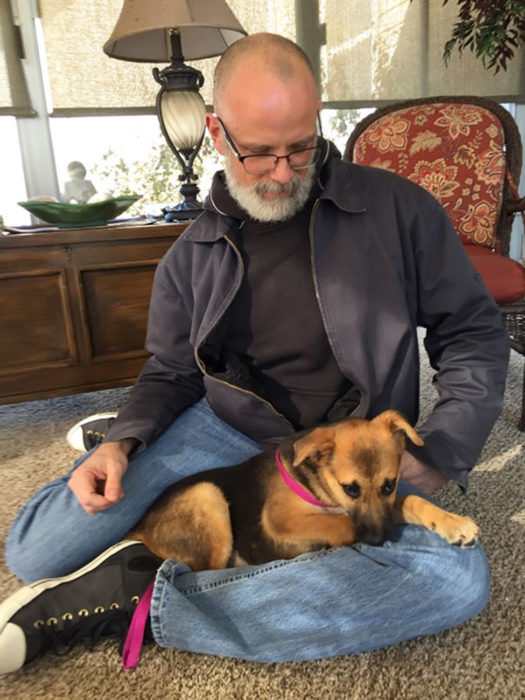 señor con canas y perro con collar rosa