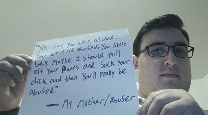 hombre sosteniendo un cartel que cuenta la historia sobre como lo abusó su madre