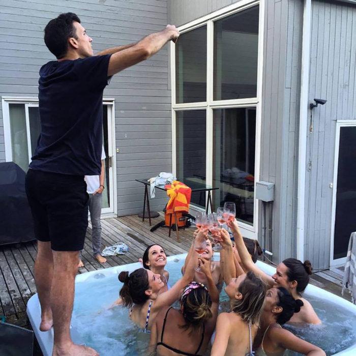 hombre tomando fotos a mujeres levantando sus copas en jacuzzi
