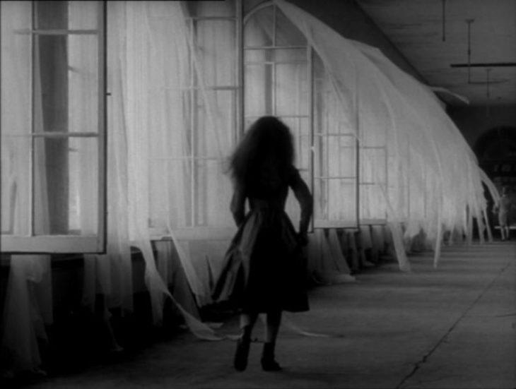 niña camina en un pasillo oscuro