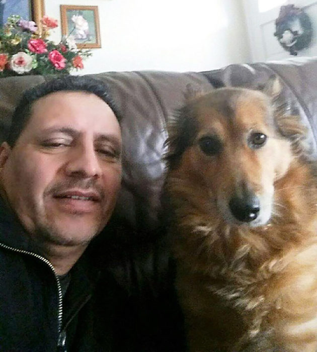 hombre sonriendo al lado de un perro