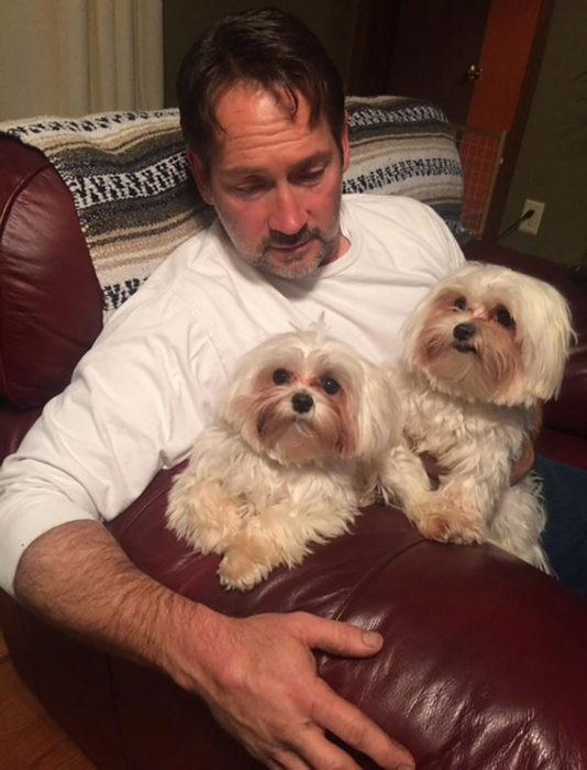 hombre con dos perros peludos