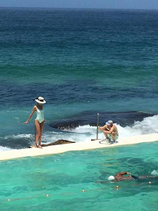 hombre tomando foto a su novia en traje de baño a la orilla del mar