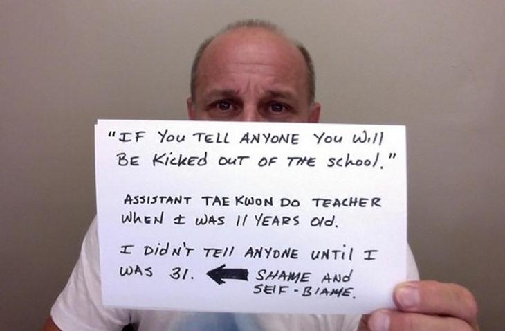 hombre sostiene cartel que cuenta como fue abusado por su maestro de taekwondo