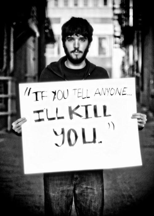 hombre sostiene cartel que dice te mataré si le dices a alguien