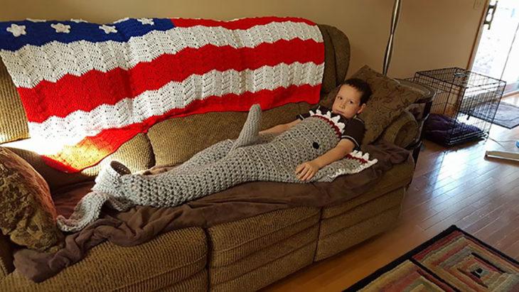 niño con una manta tejida de tiburón