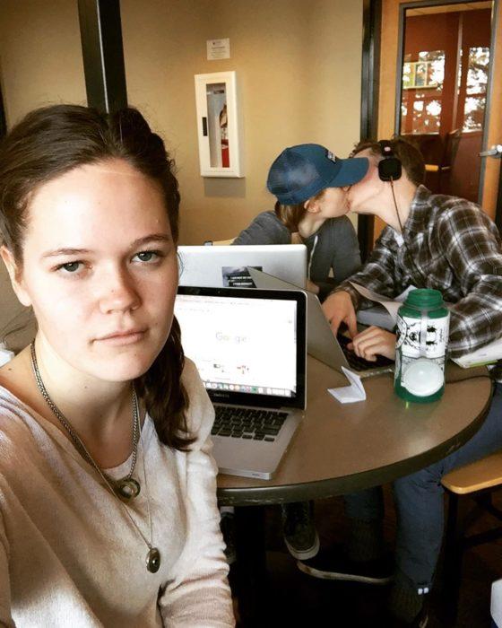 muchacha con laptop frente a una pareja que se besa en una cafetería