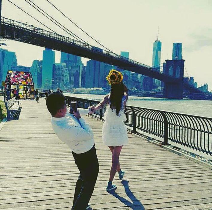 hombre tomado de la mano de su novia le toma una foto mientras ella sostiene un ramo de flores sobre su cabeza