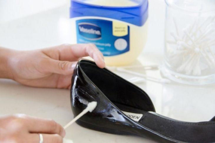 manos limpian con hisopos y vaselina zapatos de charol