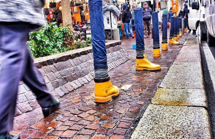 tubos con jeans y botas en una calle