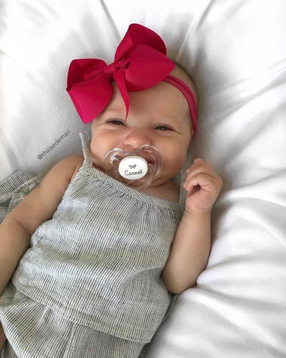 bebe sonriente con moño rojo