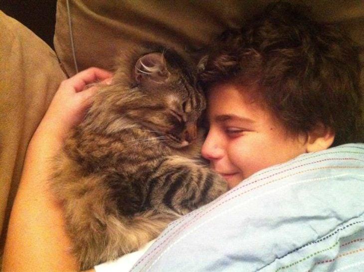niño con su gato dormidos