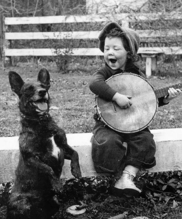 niña tocando con su banjo a un lado del perro
