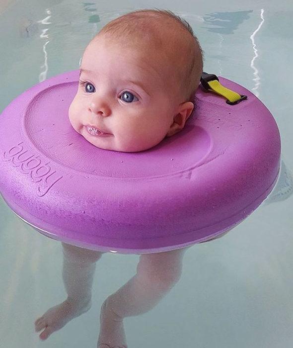 niña bebé nadando flotador rosa