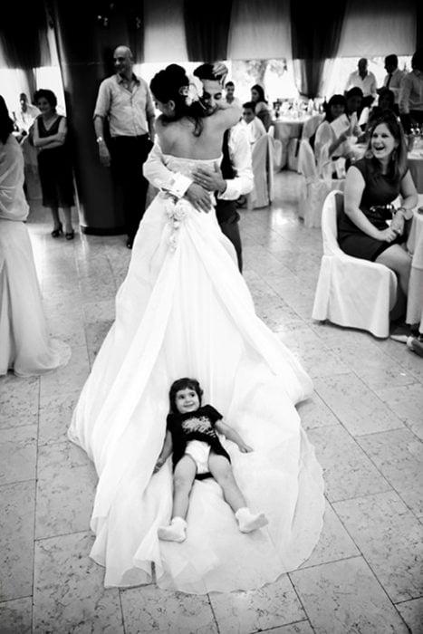 niña acostada sobre el vestido de la novia