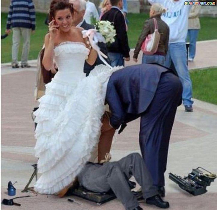dos hombres viendo algo abajo del vestido de novia de la chica