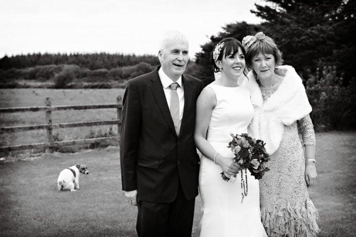 papas con su hija en su boda, perro atrás haciendo sus necesidades