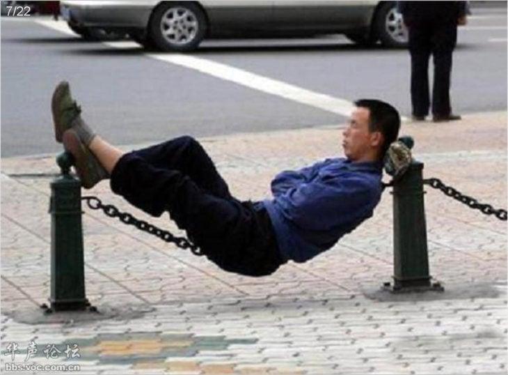 hombre recostado en cadenas en la calle