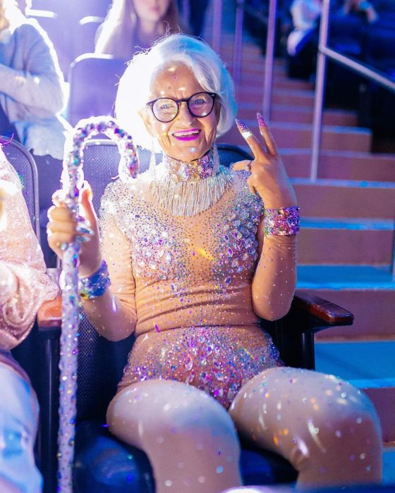 abuelita baddie con un traje pegado con brillos y un bastón lleno de brillos