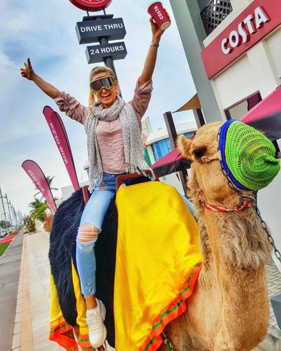 mujer montada en un camello en la ciudad