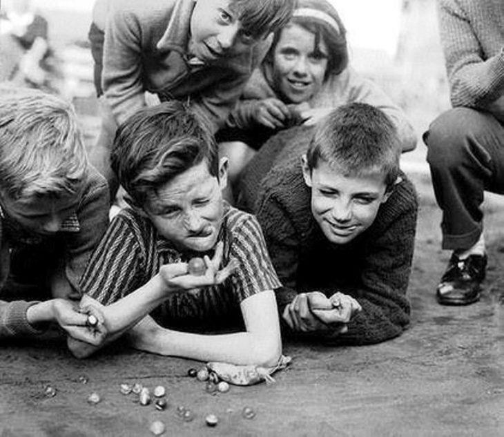 niño jugando a las canicas