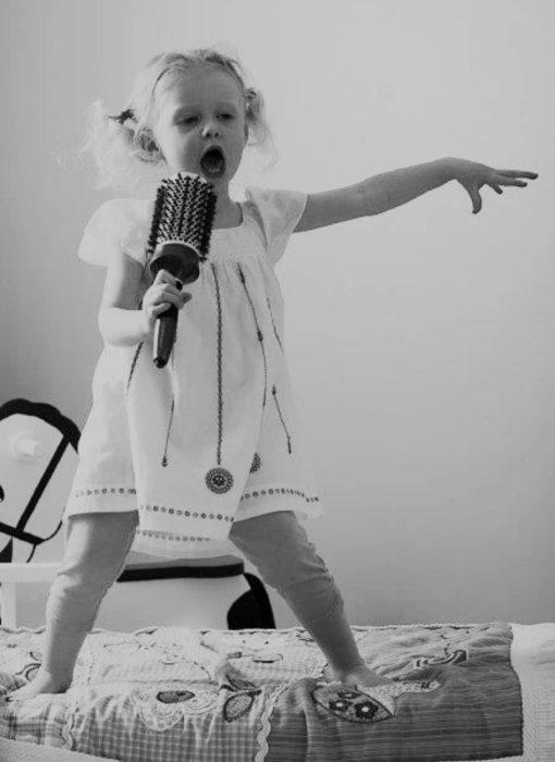 niña cantando con un cepillo