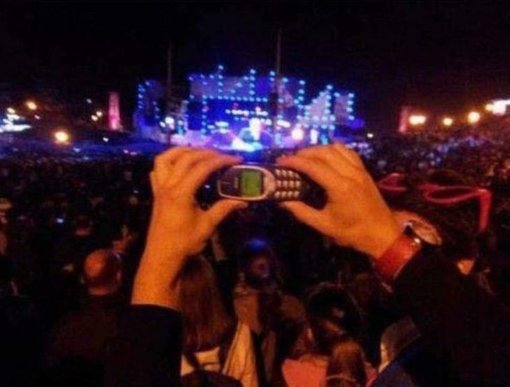 hombre sosteniendo un celular antiguo en un concierto