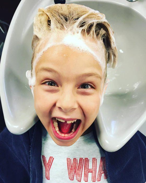 niño sonriendo con champú en el cabello