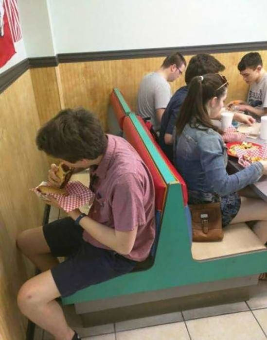 chico comiendo un burrito en una silla contra la pared