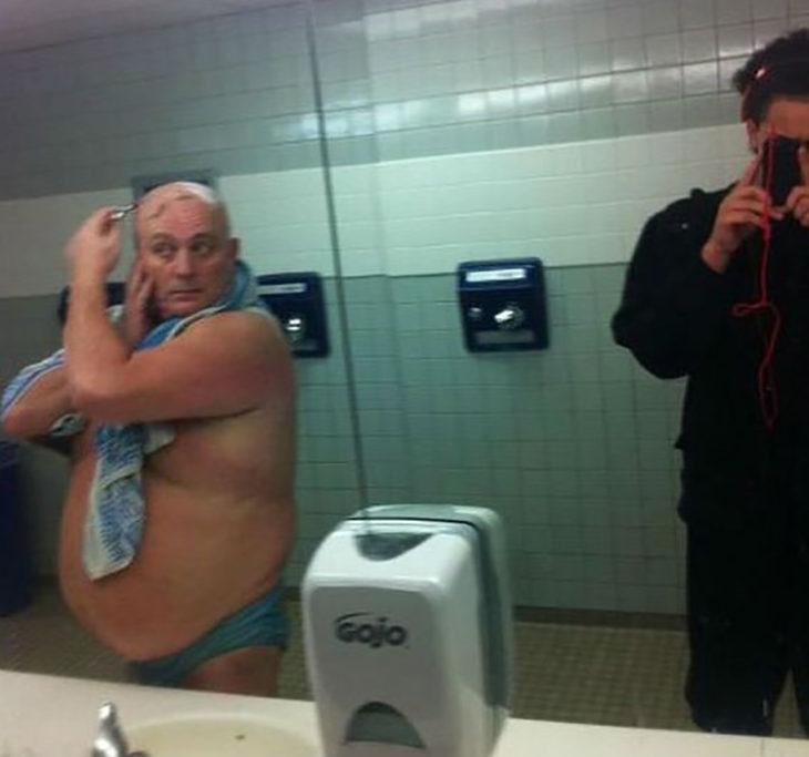 hombre rasurándose en baño público