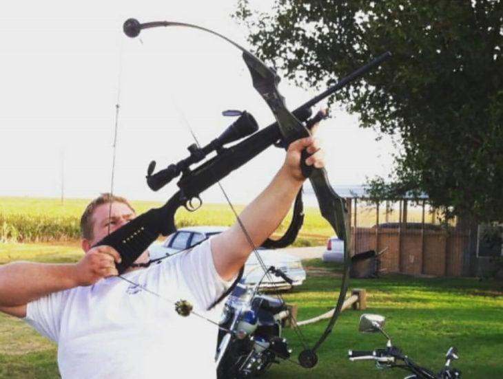 hombre con un un arco que usa como flecha una escopeta