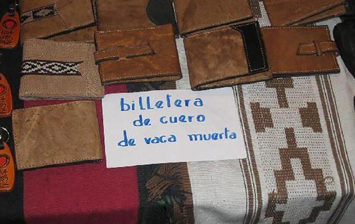 billeteras y un cartel que dice billetera de cuero de vaca muerta