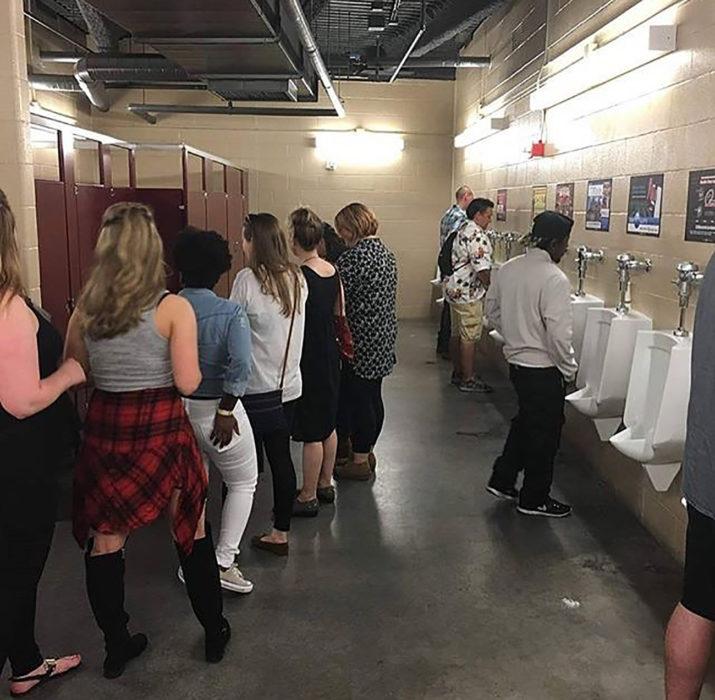 mujeres haciendo fila en el baño y a un lado están los hombres en los urinarios