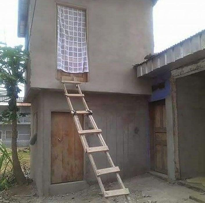casa de dos pisos en obra negra y una escalera de madera