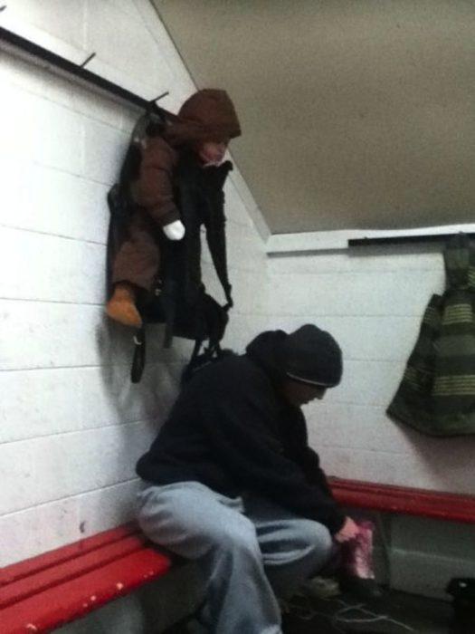 niño colgado de un tubo para sujetar mochilas