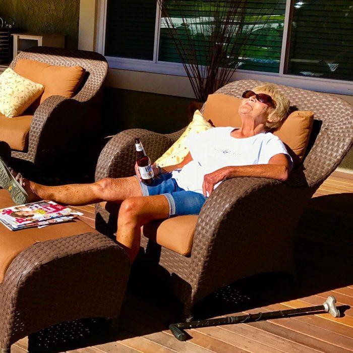 mujer mayor en sofá con una cerveza