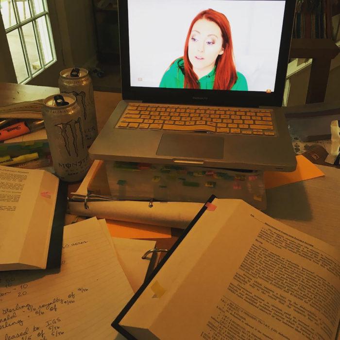 libros y laptop con chica peliroja